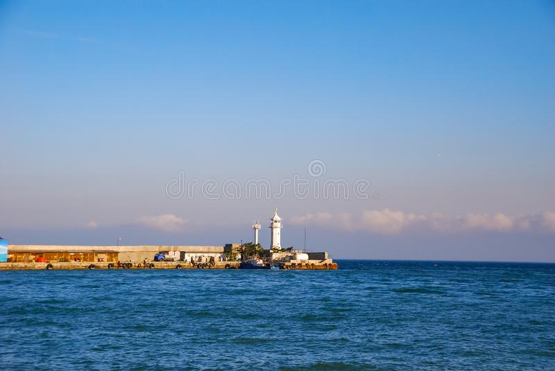 The pier in the blue sea, near which are the boats stock photos