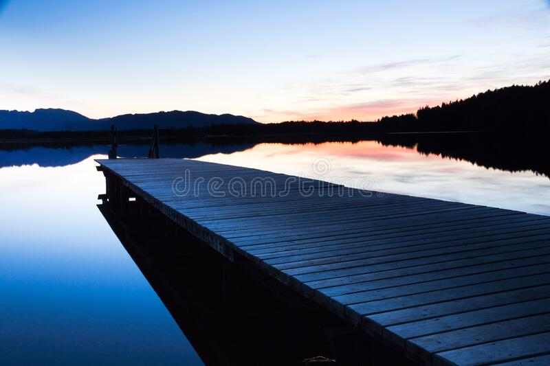 Pier on calm lake stock photo