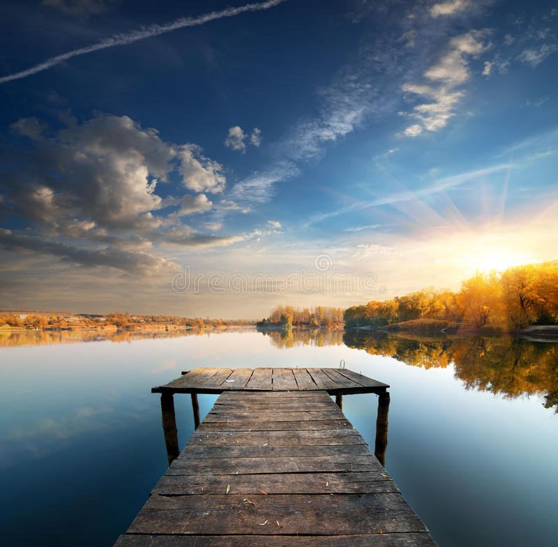 Pier on a calm river. In the autumn royalty free stock images