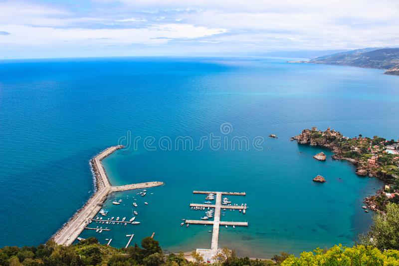 Pier by coastal Sicilian city Cefalu from above on a cloudy day. The wharf was taken from adjacent hills. Overlooking the beautiful bay. Popular tourist stock images