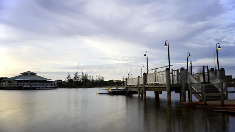 Pier On Early Morning Dusk. A view of a boat pier on an early morning sunrise on a cloudy and overcast sky. This was taken at Twin Waters Resort in Queensland in stock image