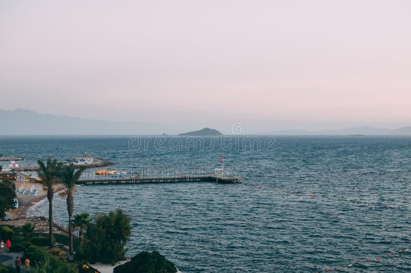 Pier en una playa de arena al atardecer en Turquía, Bodrum Verano foto de archivo libre de regalías