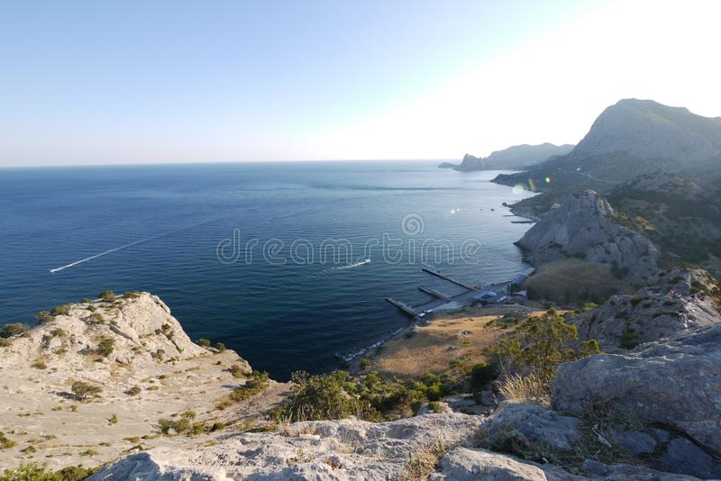 A pier at the foot of a high rocky mountain near which boats float. For your design royalty free stock images