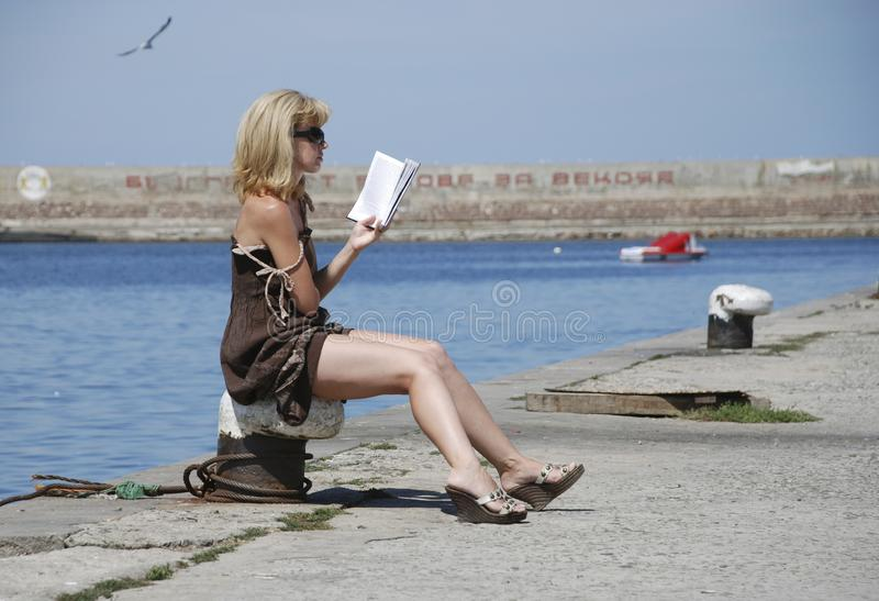 On the pier girl reading a book and sunbathing royalty free stock photo