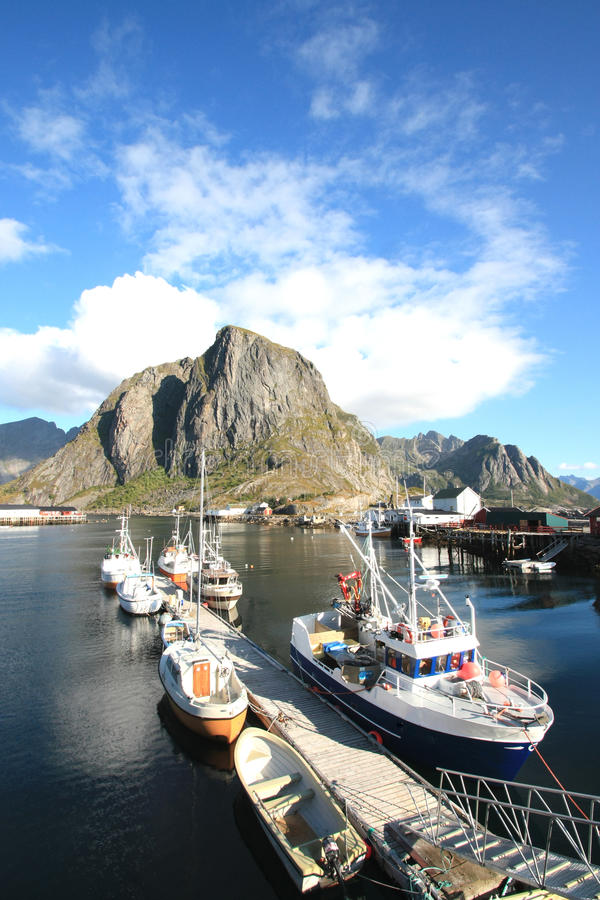 From the pier of Hamnoy's harbour. Lofts , boats, mountains and clouds mirroring in the fjord of Hamnoy in Lofoten stock photos