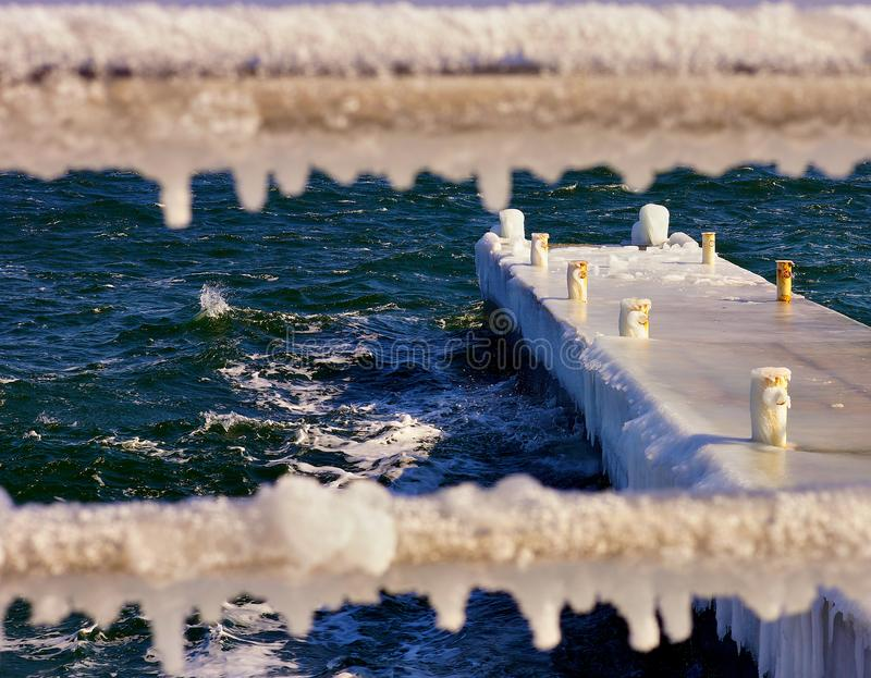Pier in the ice with defocused frozen fence. On foreground on the northern coast of the Black Sea. Odessa, Ukraine royalty free stock photography