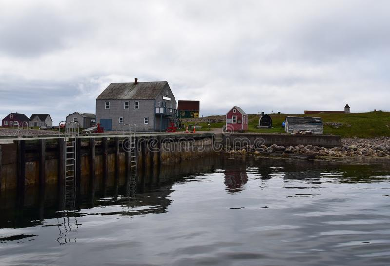 Pier at Ile aux Marin. Pier and historical buildings along the shoreline of the fishing village on the Ile aux Marin Saint Pierre, Saint Pierre and Miquelon stock photo