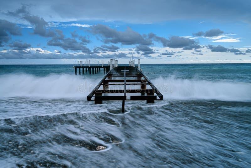 Pier im stürmischen Meer stockbild
