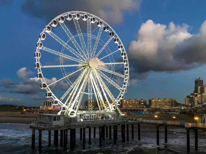 The pier jetty of scheveningen at night with the ferris wheel lighted up and view on the town. The pier jetty of scheveningen at night time with the ferris wheel stock photo