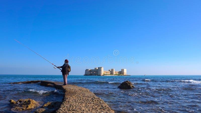 Pier with Kizkalesi Castle And woman Fishing stock photo