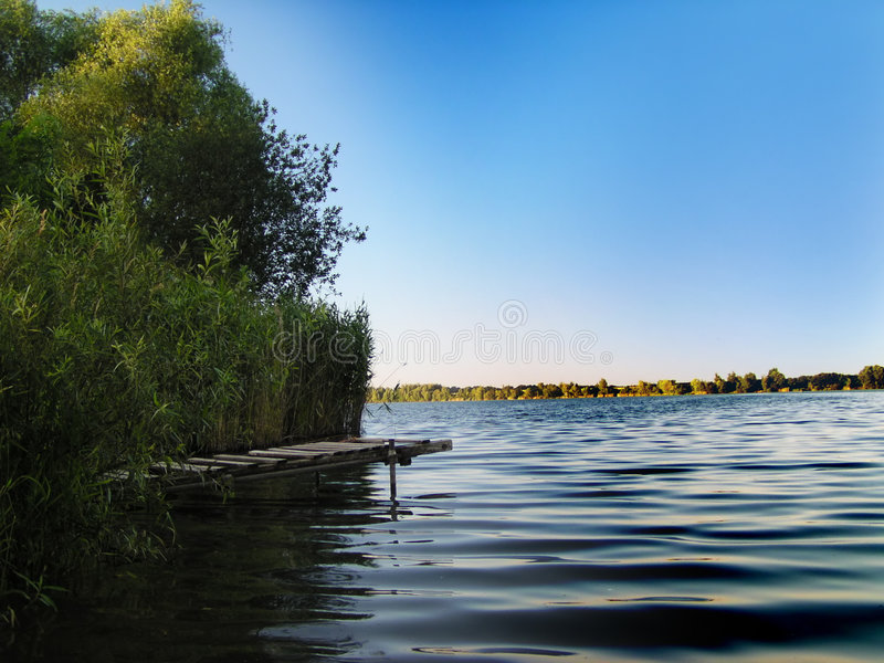 Pier in the lake. With small waves royalty free stock images