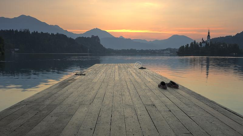 A pier on Lake Bled in warm morning light in summer. A photo of a pier on Lake Bled in Slovenia on a summer morning. Nice hills in the background stock image