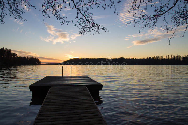 Pier and a lake in the evening light. Southern Finland lakeview in the evening light stock image