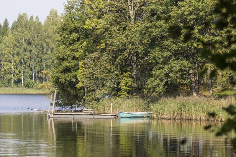 Pier at the lake. Small Fishing boat and pier at Holy Lake (Puhajärv), Otepää/ Estonia stock images