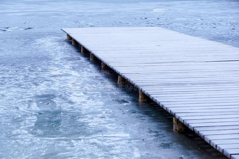 Pier on the lake. Wooden bridge in forest in winter time with blue frozen lake. Lake for fishing with pier. Dark lake royalty free stock images