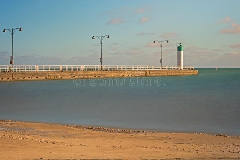 Pier At Lakeview Park In Oshawa, Ontario, Canada. Long exposure photo of the pier and lighthouse beacon at Lakeview Park in Oshawa, Ontario, Canada. View is stock image