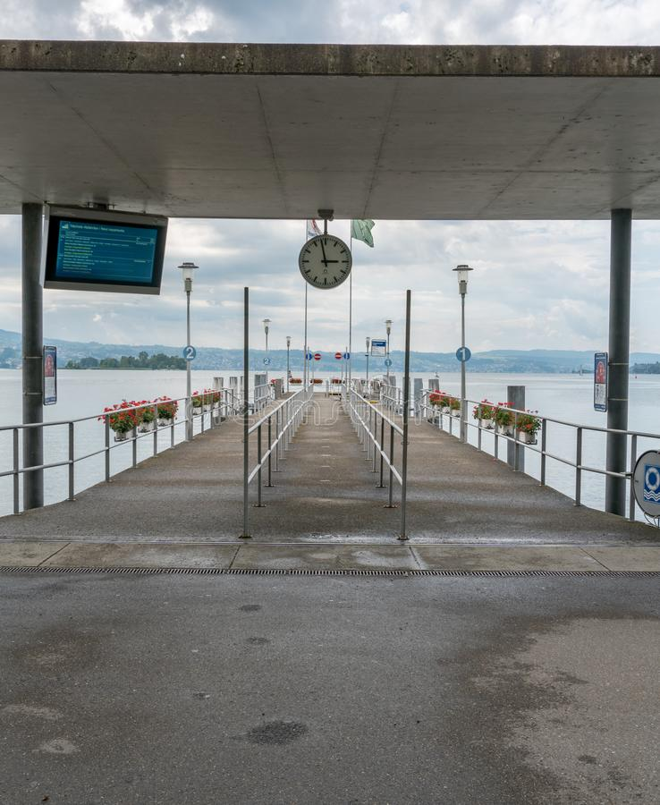 Pier and landing station for passenger ship traffic on Lake Zurich with clock and timetable. Rapperswil, SG / Switzerland - 3. August 2019: pier and landing royalty free stock photography