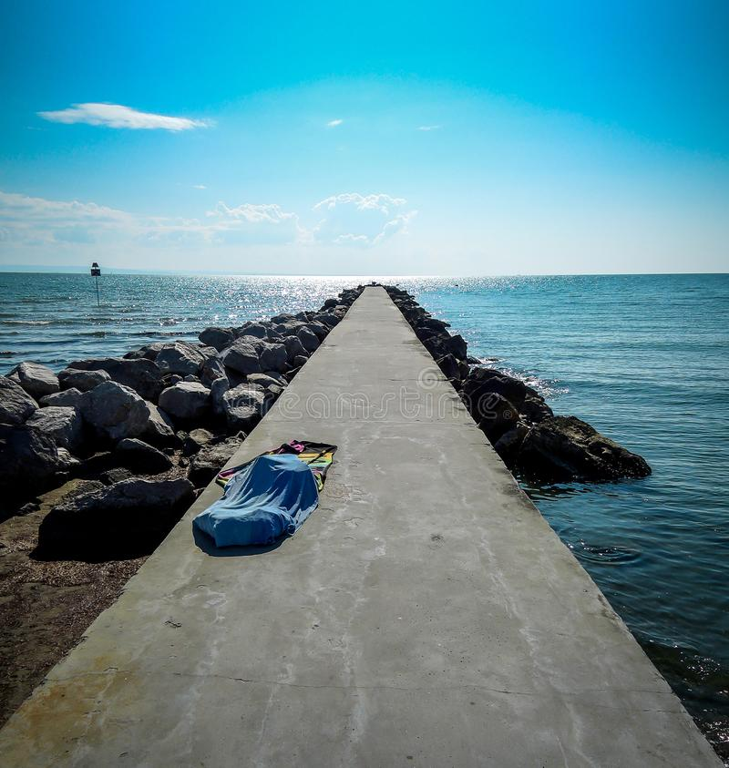Pier leading into adriatic sea in Grado, Italy with lonely towel. Perspective seascape shot in sunny daylight. stock photo