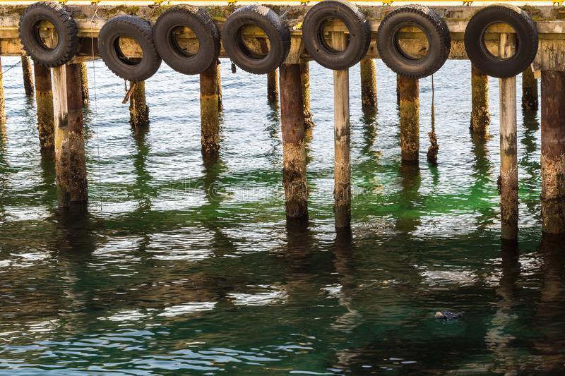 Pier lined with tires as fenders for the boats docking on them, Harstad in Norway. Pier lined with tires as fenders for the boats docking on them, close view royalty free stock images