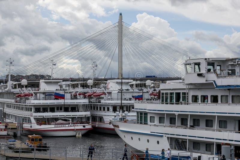 Pier met de schepen van de passagiersmotor op Neva River tegen de achtergrond van de pylonen van de Grote Obukhovsky-Brug in St P royalty-vrije stock foto