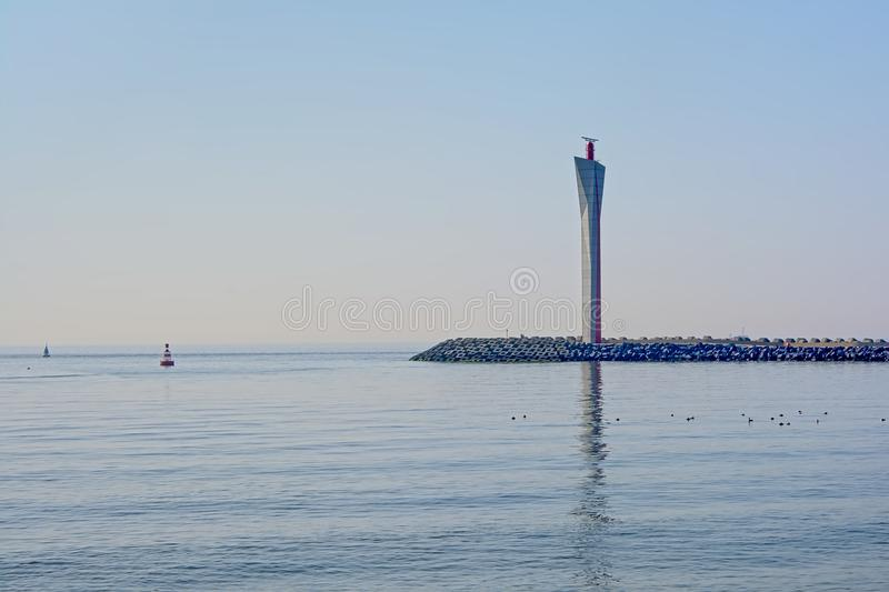 Pier with modern radar tower, reflecting in the water of the sea in the harbor of OStend, Belgium. Pier with modern radar towe, designed by E+W Eggermont royalty free stock photo