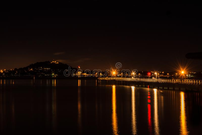 A pier at night: lamp lights, a blurry group of fishermen and a distant silhouette of Mount Victoria royalty free stock images