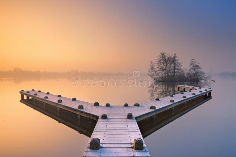 Pier op een stil meer op de ochtend van de mistige winter royalty-vrije stock afbeeldingen