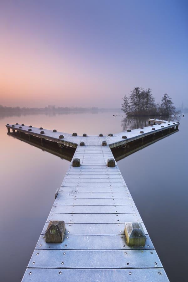 Pier op een stil meer op de ochtend van de mistige winter stock foto