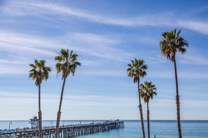 San Clemente Pier. The pier and palm trees at San Clemente beach, with a blue sky overhead royalty free stock photo