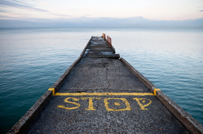 Pier perspective with yellow Stop label. Pier perspective with yellow stop-line and Stop label on Black Sea coast. Russia, Sochi, Adler stock photo