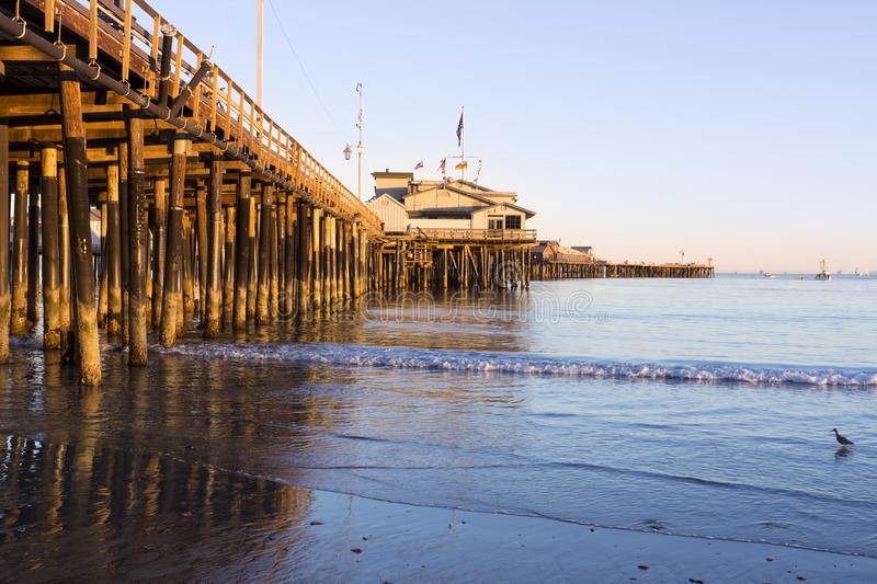 Pier in Santa Barbara. A low, setting sun casts a deep orange light on the pilings of the Santa Barbara pier, also know as Stearns Wharf stock images