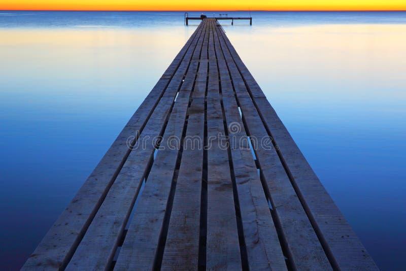 Pier on the sea during a calm. Decline during a calm over a quiet ocean smooth surface stock photos