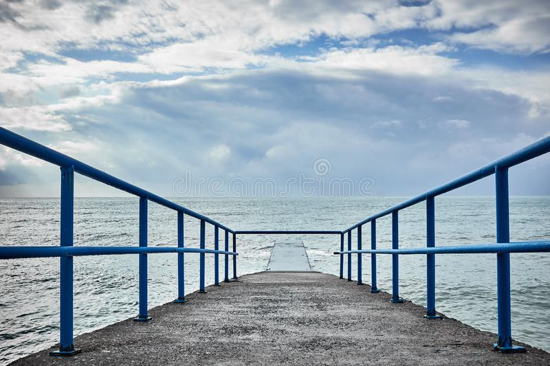 Pier and sea with sun stock image