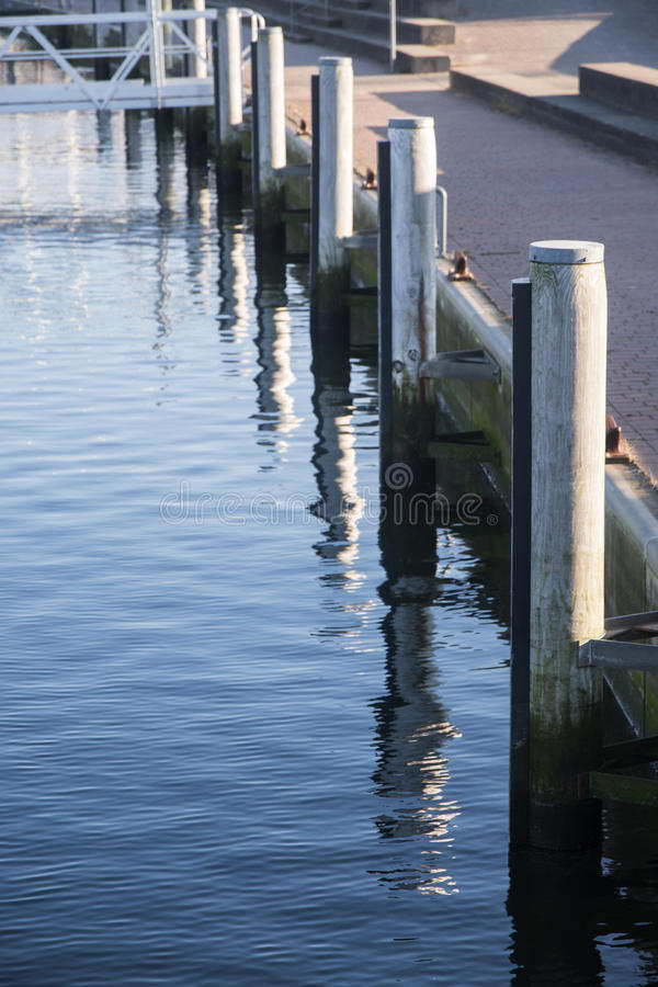 Pier shore at the marina with wooden bollards and blue sea, vert royalty free stock image