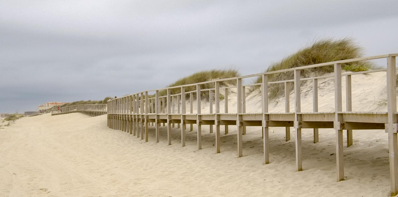 Pier sobre las dunas en la costa fotos de archivo