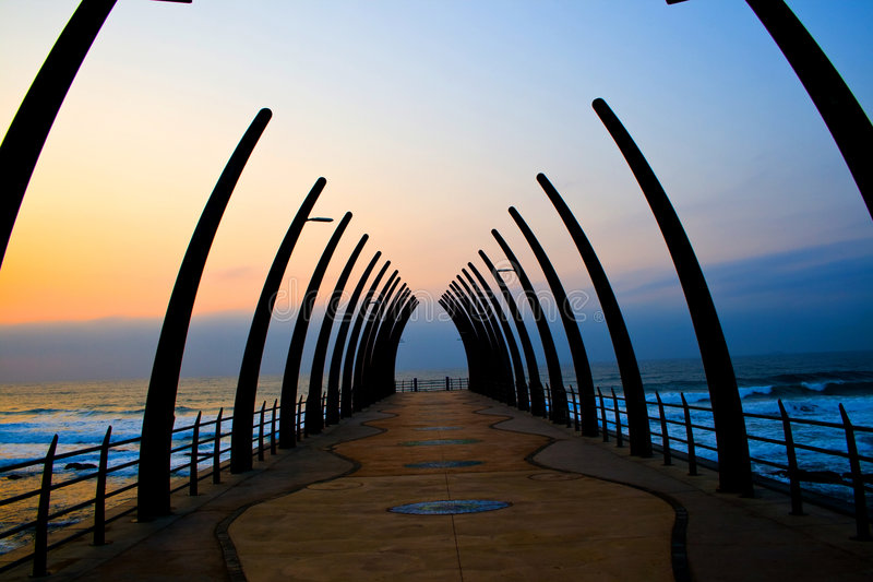 Pier at sunrise. Beautiful warm colorful sunrise over seaside pier, picture taken in Umhlanga beach, Durban, south africa stock photography