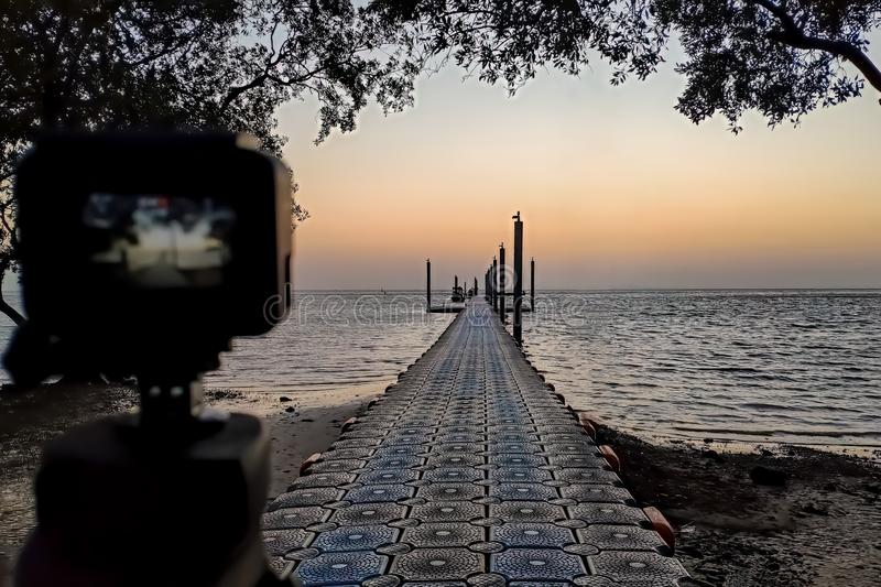 The pier and sunrise on the sea. Camera mounted on a tripod at foreground defocused.  stock image