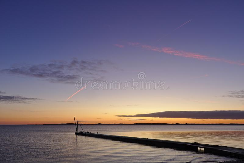 Pier before sunrise with small crane silhouetted against the morning sky and red vapor trail overhead stock image
