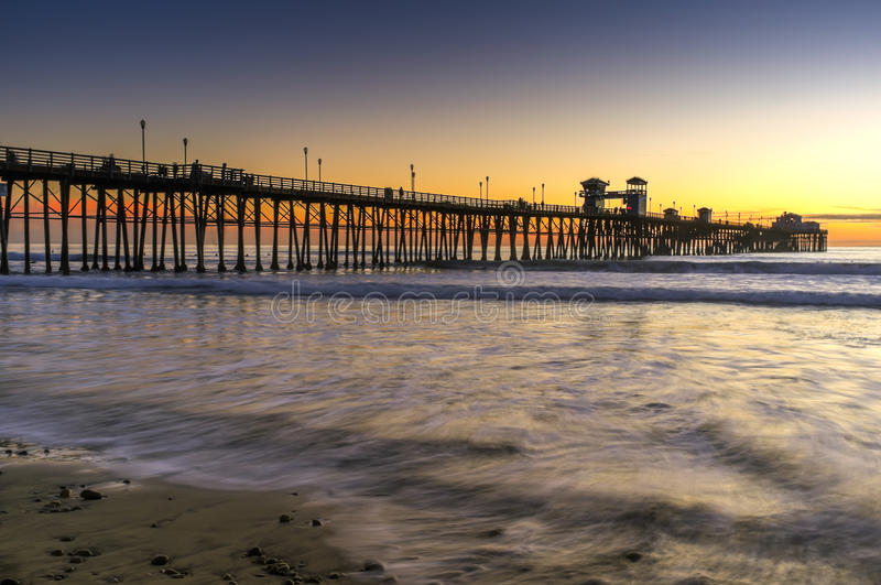 Pier at Sunset, Oceanside California. The wooden pier juts into the waters of the Pacific Ocean near a beach in Oceanside, north San Diego County, southern