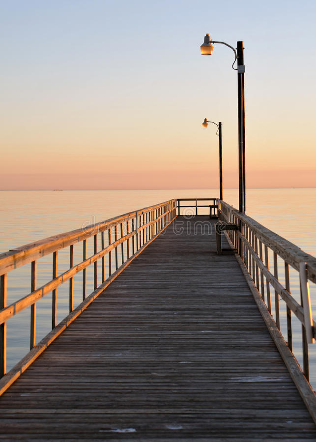 Pier at Sunset in Soft Pastels. Pink and blue royalty free stock photos