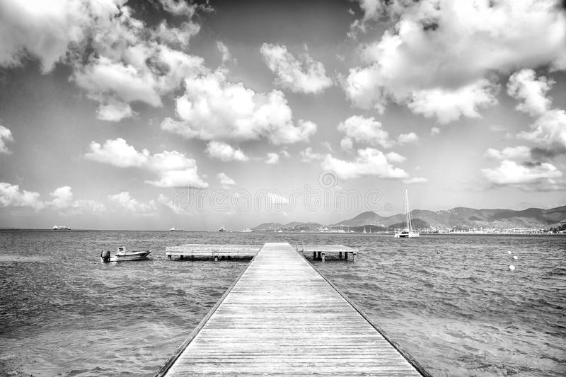 Pier in turquoise sea and blue sky with white clouds in philipsburg, sint maarten. Freedom, perspective and future stock photos
