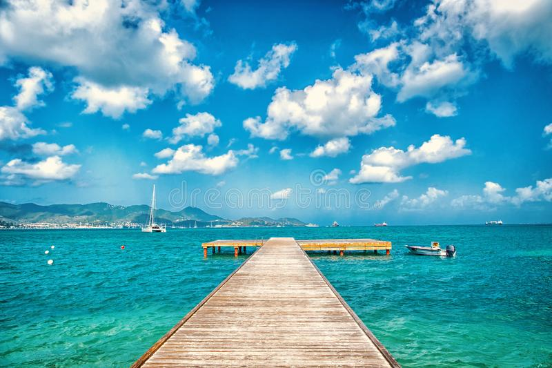 Pier in turquoise sea and blue sky with white clouds in philipsburg, sint maarten. Freedom, perspective and future. Beach vacation at Caribbean, wanderlust stock photos