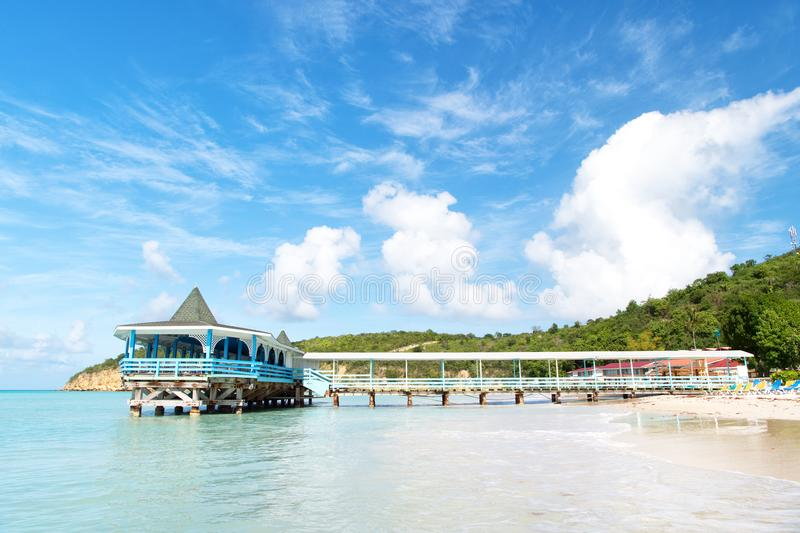 Pier in turquoise water on blue sky background. Sea beach with wooden shelter on sunny day in antigua. Summer vacation on caribbea royalty free stock photos