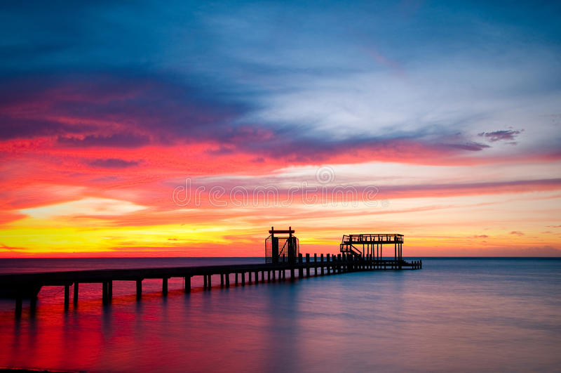 Pier und bunter Ozeansonnenuntergang lizenzfreies stockbild