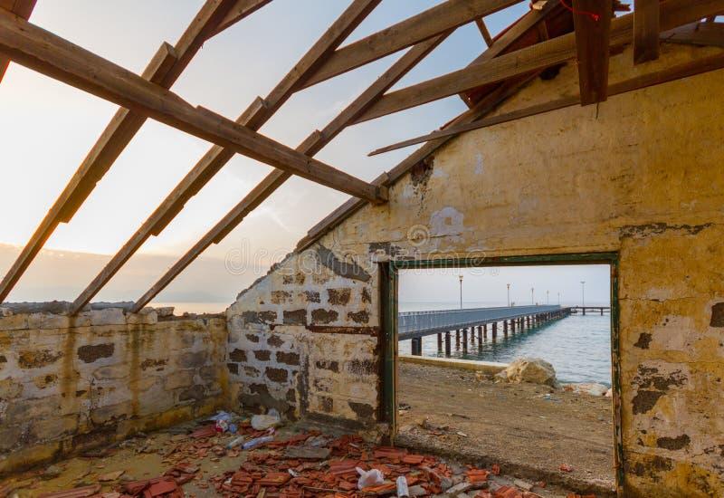 Pier- und Seeansicht durch aufgegebenes Haus durch den Strand lizenzfreie stockfotografie