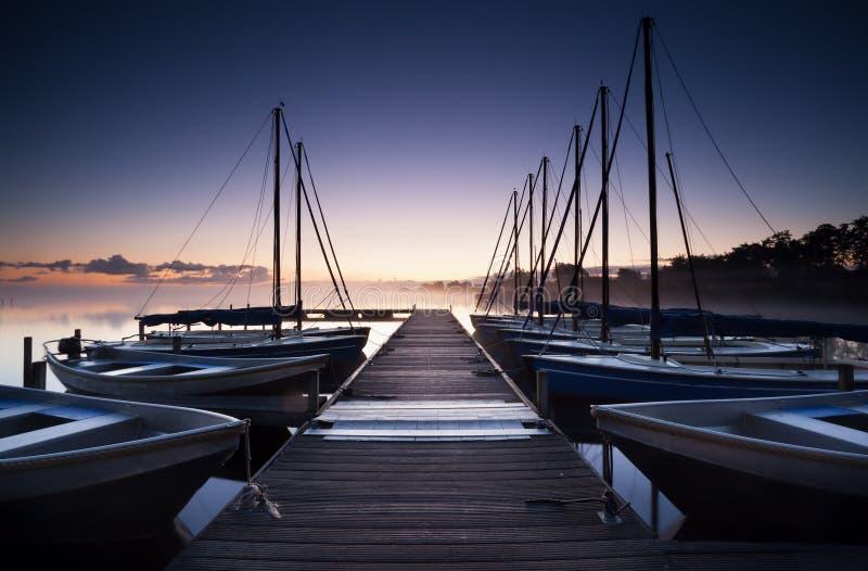 Pier und Yacht auf See bei Sonnenaufgang lizenzfreie stockfotos
