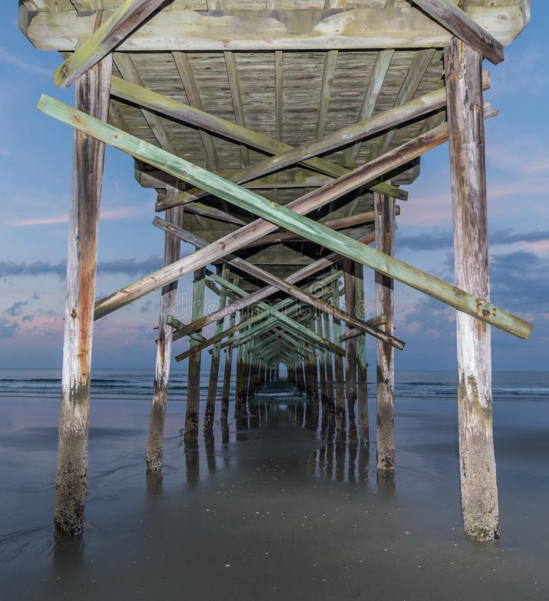 Pier. Under the ocean isle fishing pier. Build to withstand the waves from the ocean stock photography