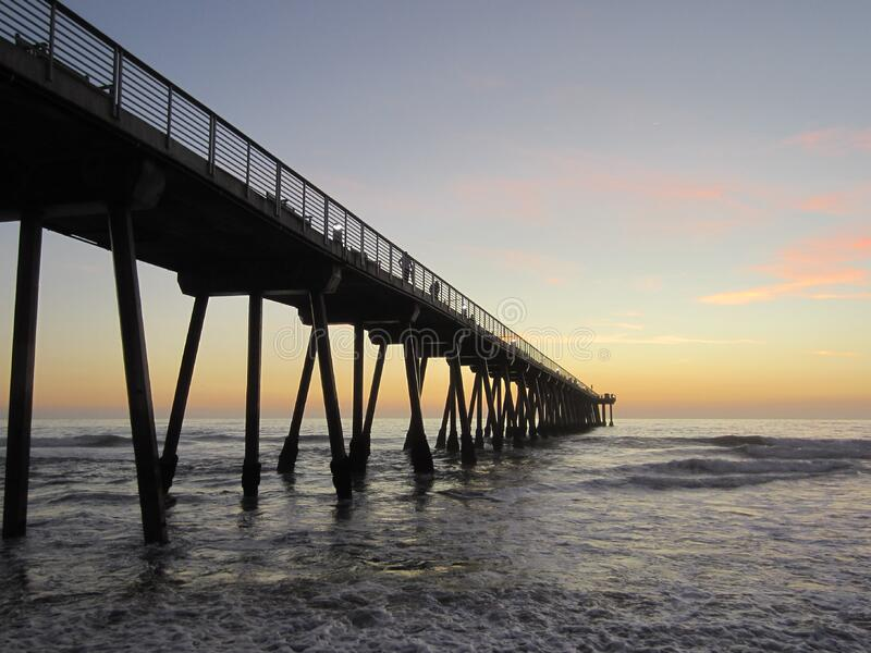 Pier in water at sunrise stock photos