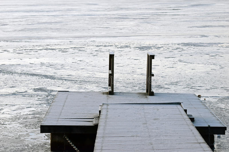 Pier on winter. Swimming dock on frozen lake royalty free stock images