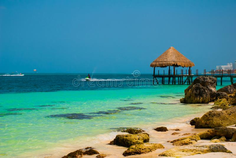 Pier and wooden gazebo by the beach. Tropical landscape with Jetty: sea, sand, rocks, waves, turquoise water. Mexico, Cancun. Paradise royalty free stock photos